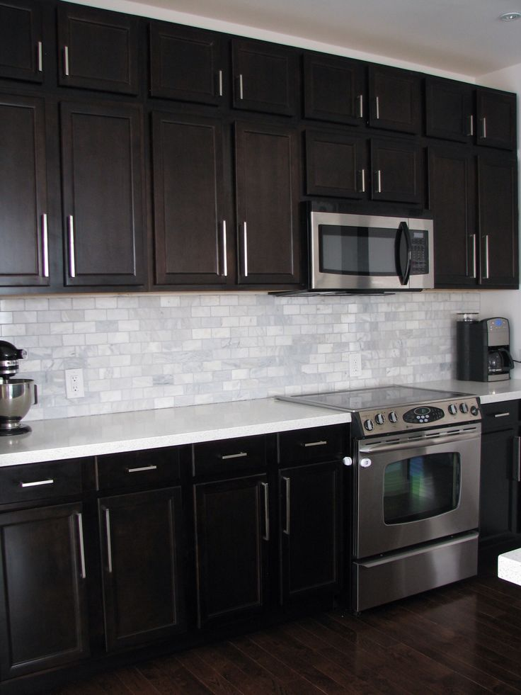 Dark birch kitchen cabinets with shining white quartz counters and white marble backsplash - White kitchen dark counters ...