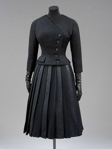 "Suit, Hubert de Givenchy, Paris, France: 1955, wool with moiré silk panels in the skirt. ""This ensemble was designed by the Parisian couturier Hubert de Givenchy (b. 1927) for Leslie Caron (b. 1931), the French film actress and dancer. It was made for a play called 'Orvet' by Jean Renoir, who was Caron's great friend and mentor. He wrote it for her, and also directed it. It was first performed at the Theatre de la Renaissance, Paris, on 12 March 1955."""