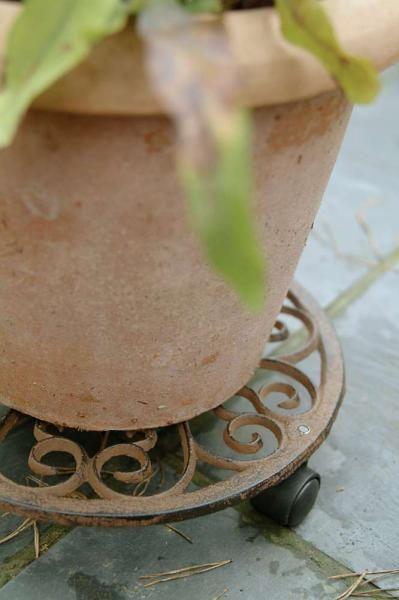 Klasszikus mintájú kerek öntöttvas, gurulós virágcseréptartó három műanyag kerékkel. Segítségével könnyebbé válik a nagy méretű virágcserepek mozgatása, áthelyezése