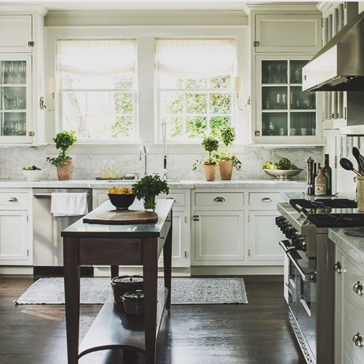Things I love about this kitchen: the non-island island, the sconces on the sides of the cabinets framing the sink, classic white inset cabinets with glass fronts, the vintage style latch hardware on the uppers, that it could have been published 20 years ago and still look current. Classics never age ( via @southernlivingmag , designed by @phoebehoward_decorator ) #nshinspiration