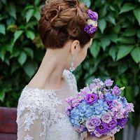 Высокая собранная прическа и букет невесты в голубых и сиреневых оттенках из роз эустом и фиалок