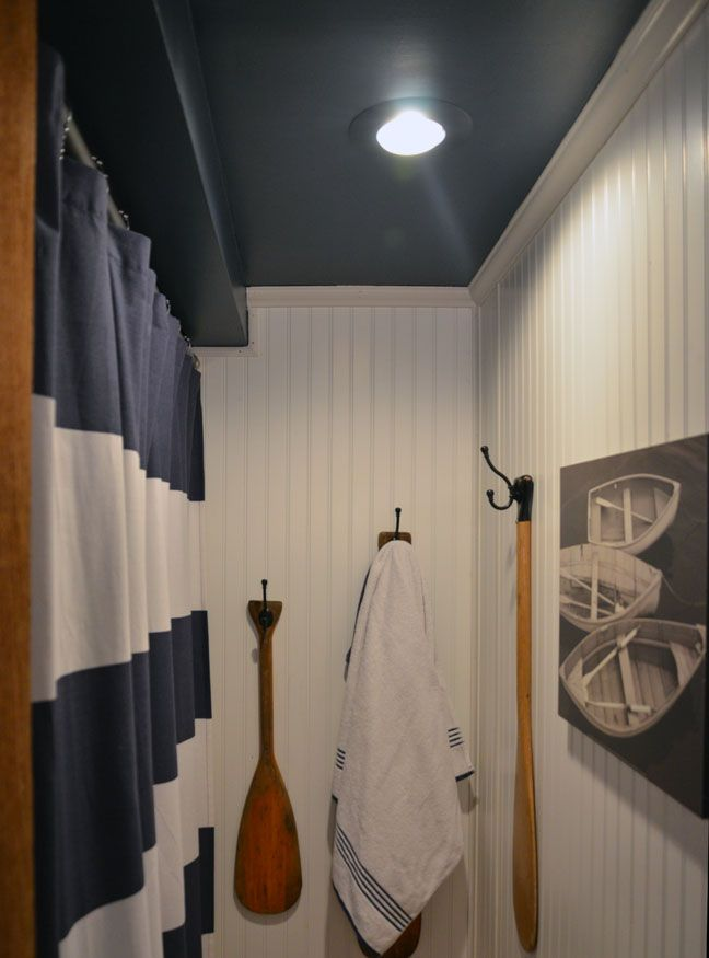 Big impact in a tiny space: nautical theme bathroom with striped shower curtain, canoe paddle towel hooks