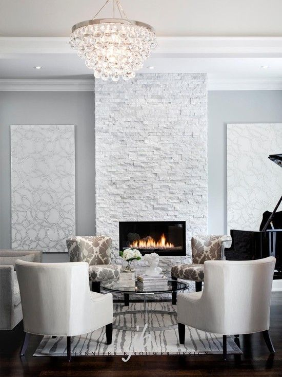 Bling chandelier hangs in front of modern grey stone fireplace
