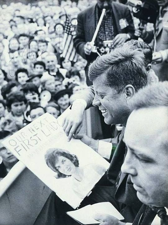 1960: JFK looks at a picture of Jackie.
