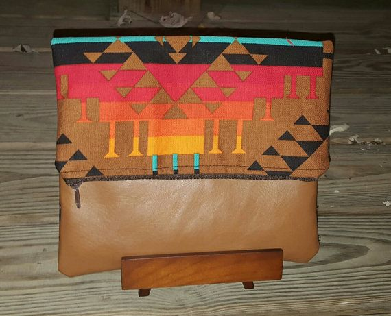 Multicolor Aztec fold over clutch with tan base orange pink black blue very nice. https://www.etsy.com/listing/248006626/multicolor-aztec-fold-over-clutch-purse