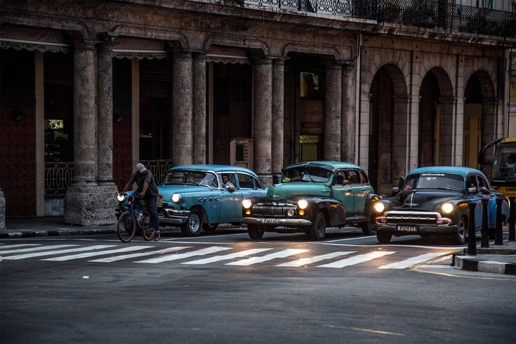 cuba vintage cars lined up at a zebra crossing in front of a portico