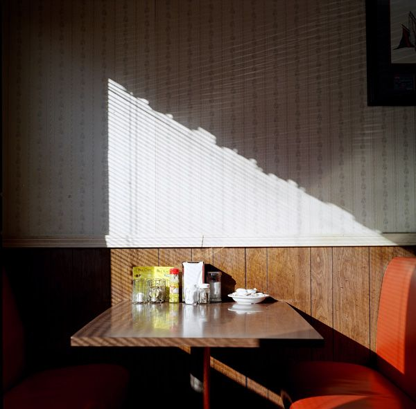 Photographer, Lisa Scheer, captures light patterns shining on an empty booth. The shapes created illuminate the mundane scene into an expressive and characterful image.