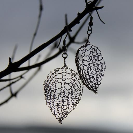 """The idea for these copper wire earrings arose out of a desire to be able to wear some form of hand-knitting to evening functions where a sweater or mittens aren't quite appropriate! For the knitter who enjoys a challenge.  Designer: Lucy Neatby  Size: 1.25"""" x 0.75"""""""