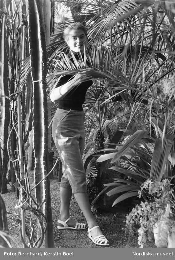 Modell klädd i capribyxor i manchester, polotröja och vita sandaler i djungelmiljö. Foto: Kerstin Bernhard, 1955