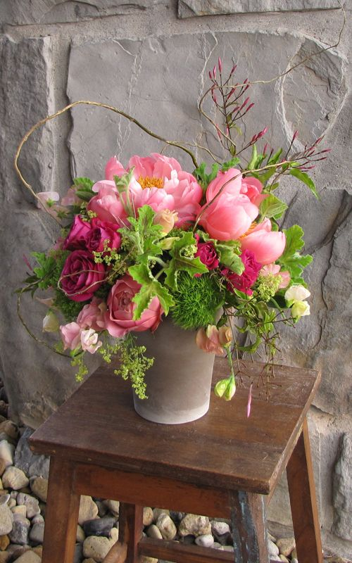 "Centerpiece with curly willow branches, jasmine vine, David Austin ""Darcey"" garden roses, Hot Majolika spray roses, Coral Charm peonies, Romantic Antike garden roses, peach sweet peas, alchemilla, Green Trick dianthus, scented geranium and Jade trachelium"