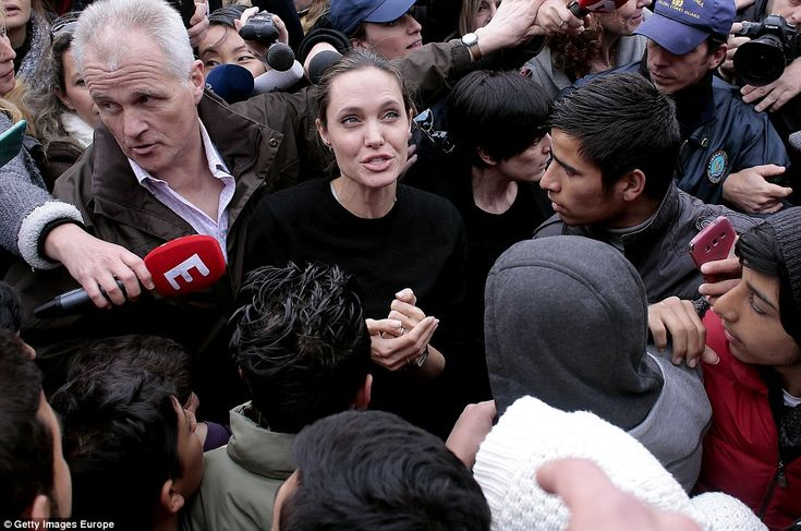 Mobbed: Angelina Jolie is surrounded by excited migrants and members of the press on a visit to a temporary migrant camp in Athens