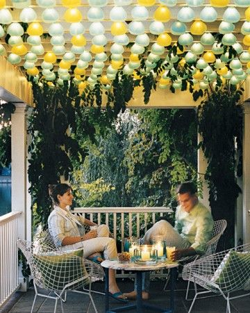 Shaded String Lights - Holiday strands trace every slat of a porch trellis; the bulbs are covered in shades made from chartreuse and turquoise vellum. The table is lighted by pillar candles, each protected by two vases (one inside the other); blue-tinted water fills the space between glasses.