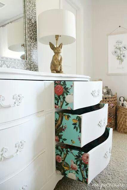 Floral wallpaper on sides of dresser drawers.