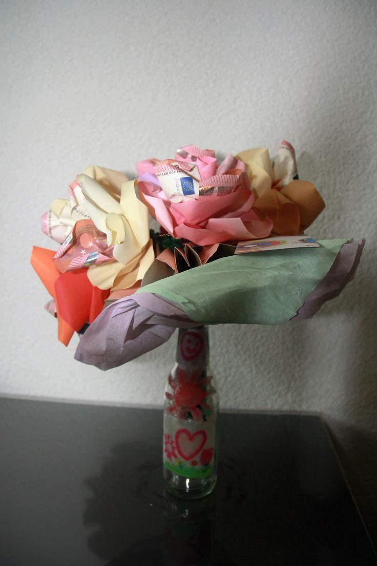 Een bosje geldbloemen op een door de kinderen versierd flesje als vaasje: een bloem met € 10 voor iedere 10 jaar