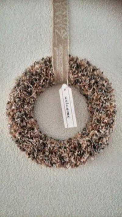 Krans gemaakt van ring van steekschuim en servetten (alles te koop bij Action). Knip de servetten in stukjes van 4 x 4 cm. Leg 3 vierkantjes (speels) op elkaar en prik ze met de platte kant van een satérprikker in de ring van steekschuim. Ik heb de krans afgewerkt met een bijpassend stuk lint (op klos) en een hanger (ook van Action).