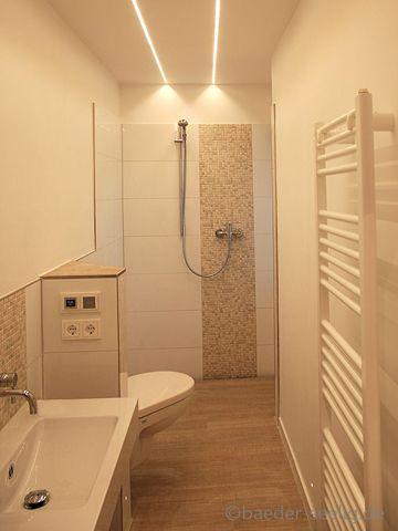 Das Bad hat die Maße 3,65m x1,10m. Die geflieste Dusche hat eine Ablaufrinne. Die Holzdekor-Fliesen mit rutschhemmender Maserung. Die Beleuchtung ist mit LED Lichtbänder hergestellt.