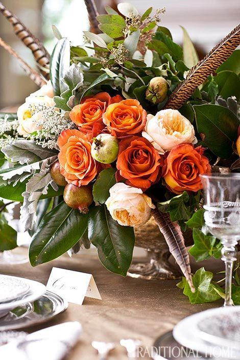 Quail feathers add interest to a floral centerpiece on a holiday table.  - Traditional Home® / Photo: John Bessler