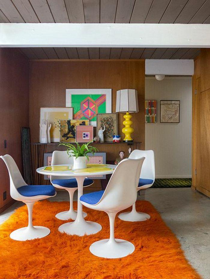 chaise tulipe, chaises blanches et tapis orange dans une salle à manger art