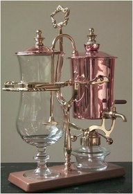 """The Genuine Balancing Syphon Coffee Maker"" by Hammacher Schlemmer        An alcohol burner heats water inside the copper kettle to 212º F, causing it to pass through the pipette and into the lead crystal brewing chamber where it steeps the coffee grounds at the ideal temperature for making rich, complex coffee."