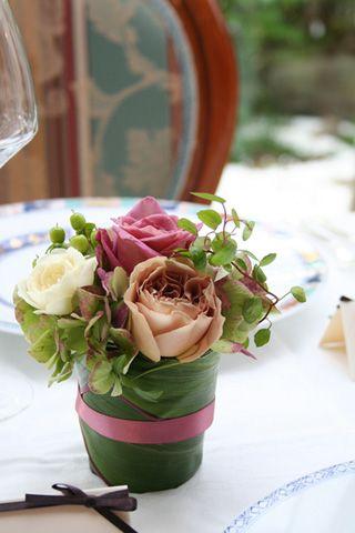 ゲストテーブルにはお料理の邪魔をしないよう、ベージュピンクやブラウン系のバラの小さめアレンジを。