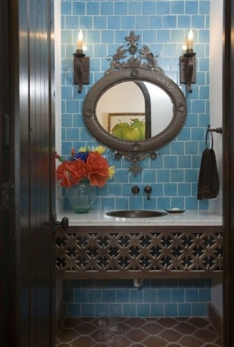 An unusual iron console sink looks Old World and suits a Spanish style bath. This frame conceals most of the plumbing.