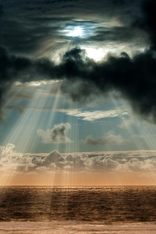 Amazing rays of sun streaming through clouds over the ocean!