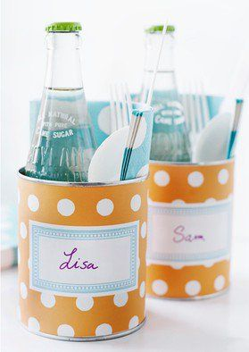 Old vegetable cans wrapped in scrapbook paper  to hold drink, napkin & utensils.