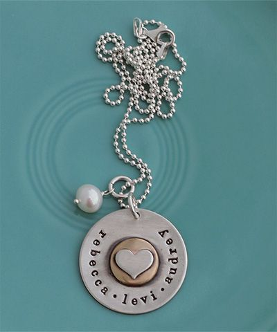 "I love it ~ $79usd golden love.    A touch of gold makes this piece a true treasure!    A 1 1/8"" outer circle is layered with a gold filled circle and a sterling heart. Any names or dates are handstamped around the edge.     Fits up to about 32 letters/spaces.    Hung on a sterling chain with a freshwater pearl."