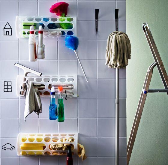 Drei VARIERA Tüten-/Rollenspender in Weiß übereinander an einer Wand mit weißen Fliesen befestigt und mit Reinigungsprodukten gefüllt. Auf die Fliesen daneben sind Symbole für den jeweiligen Inhalt gemalt.