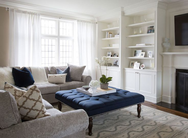 Elegant living room features traditional fireplace under flatscreen TV flanked by built-in bookcases alongside gray velvet sectional sofa with rolled-arms adorned with navy velvet pillows, gray velvet pillow and trellis pillow placed in front of navy blue tufted ottoman coffee table atop white and blue print rug.