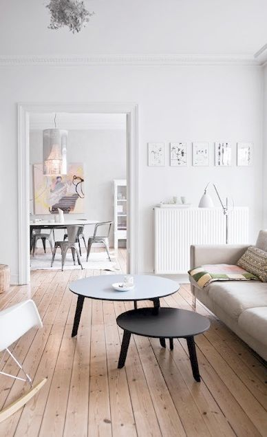 Salon esprit scandinave - murs blancs et parquet clair, mobilier simple, petites tables rondes.