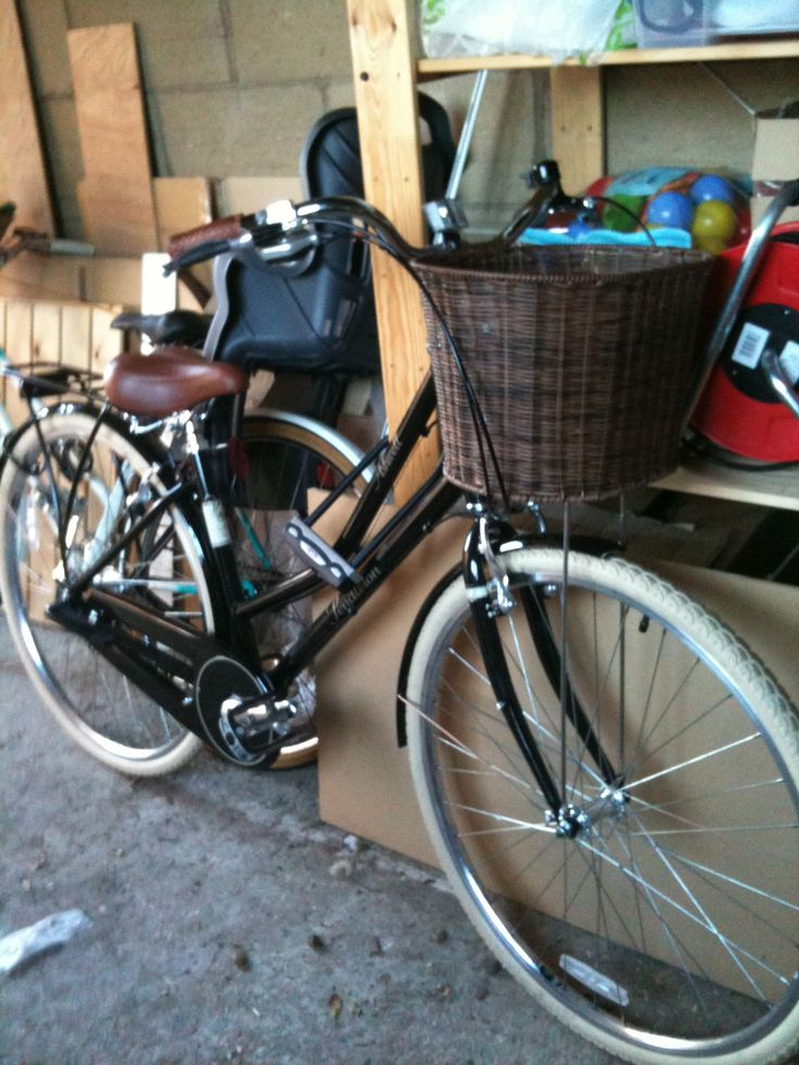 Victoria Pendleton bike. With brown leather saddle and handle grips and a dark brown wicker basket
