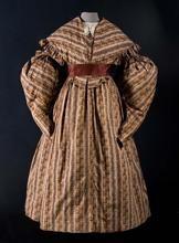 Biedermeier jurk van bedrukt katoen met schapenboutmouwen, bruin met rood-groen gebloemd banen en bijpassende pelerine kraag met ruche (B)