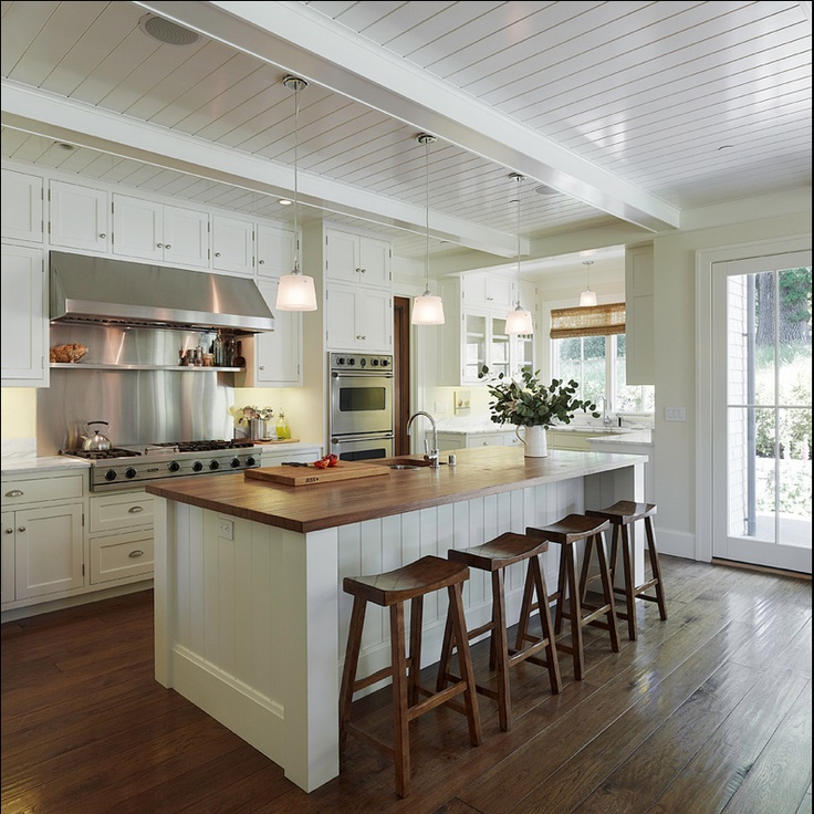 White cabinets, butcher block island, saddle stools, plank ceiling