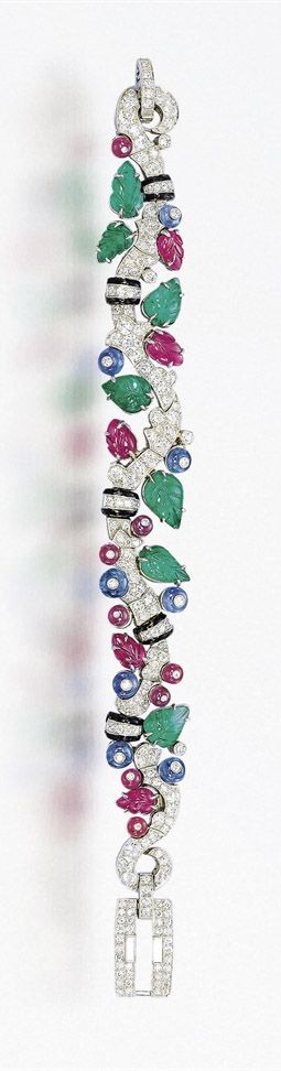 A SUPERB ART DECO SAPPHIRE, EMERALD, RUBY, ENAMEL AND DIAMOND 'TUTTI FRUTTI' BRACELET, BY CARTIER The flexible foliate band, designed as a pavé-set diamond meandering vine with black enamel rondelle details, set with carved emerald and ruby leaves and diamond inlaid sapphire and ruby buds, to the circular and baguette-cut diamond buckle-shaped clasp, mounted in platinum, made in 1933, 17.3 cm long Signed Cartier