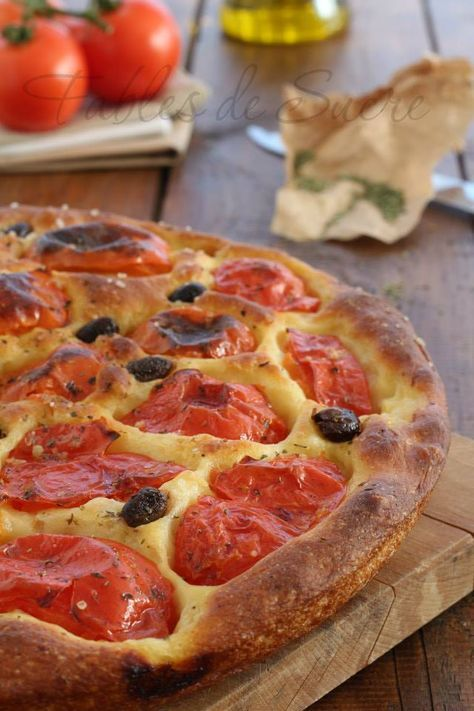 "This is an example of a traditional food. It is called ""focaccia"" and the ingredients are bread, tomatoe, cheese and olives."