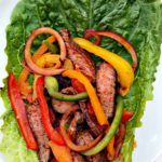 Healthy, low-carb steak lettuce wraps made with juicy, grilled sirloin steak, red onions, and an assortment of green, yellow, orange, and red peppers.