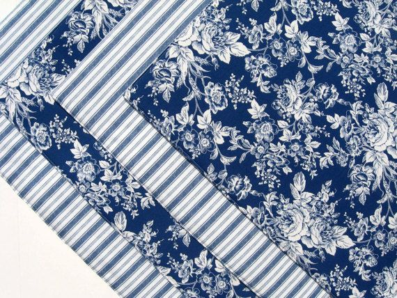 A set of four reversible, heat-resistant, blue and white placemats. One side of each is a romantic floral print. The reverse side is a striped