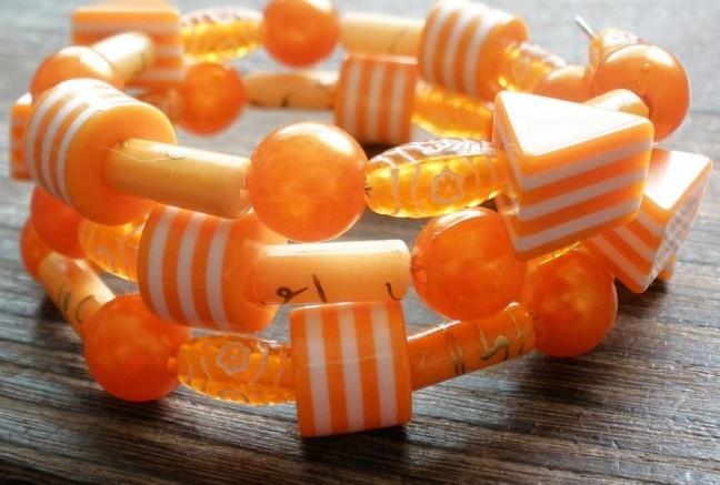 Veselý náramok s rôznymi kúskami plastových korálok a perlí na pamäťovom drôte.