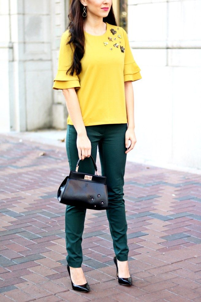 Ruffle Sleeve Top with Emerlad Green Pants and Floral Black Handbag and Black Pointed Toe Heels. Street style. Yellow top. Green pants. Green and yellow outfit. Fall fashion. Street wear. Best of Pinterest fashion. Mustard yellow top.