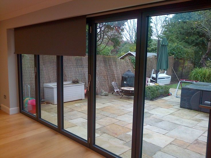 Roller Blinds Against Bifold Doors In A Living Room