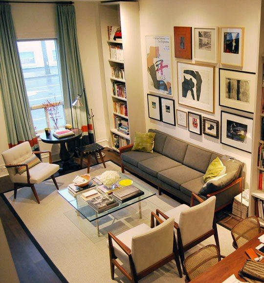 high ceiling; essential furniture; bookcase; lots of framed items.