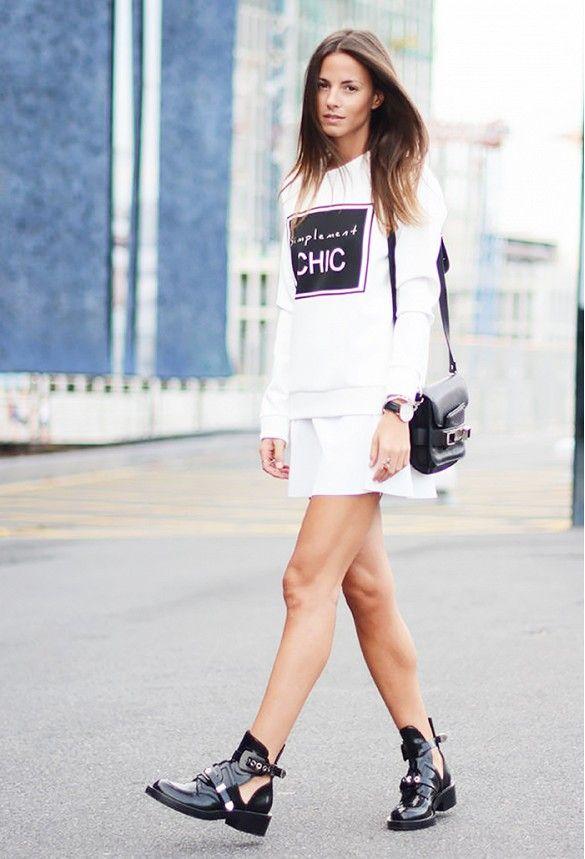 Zina Charkoplia of FashionVibe wears a graphic white sweatshirt, mini skirt, black Balenciaga boots, shoulder bag, and layered jewelry