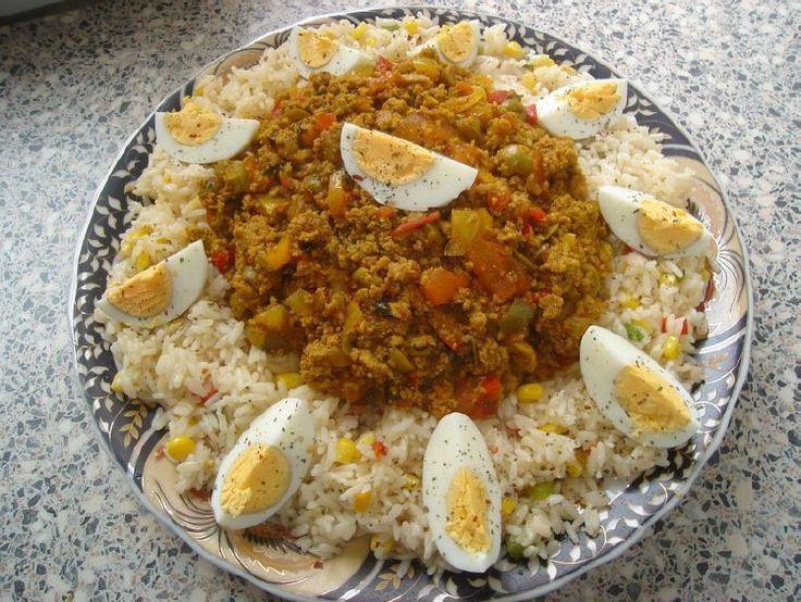Recept voor gekruide rijst met gehakt en groenten. Rul het gehakt in een pan samen met wat olie, de ui en knoflook. Voeg de paprika en tomaat toe en bak