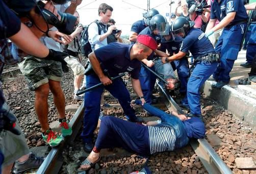 Hungary, Sept. 3, 2015: exhausted refugees being beaten by Hungarian police