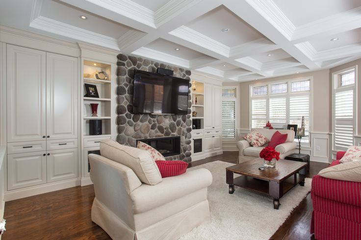 This beautiful living space has a feature stone wall with ribbon gas fireplace. The large windows allow for natural light during the day, while the pot lights in the coffered ceiling illuminate the area in the evening.