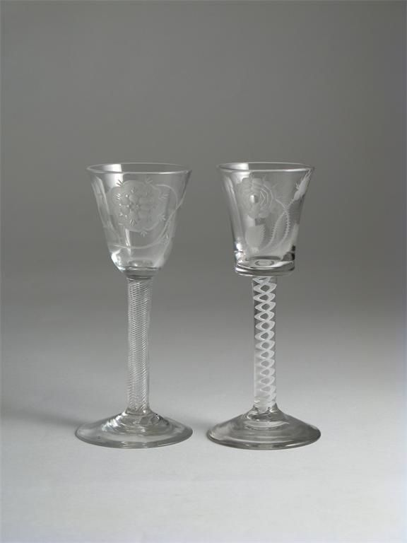 Two wine glasses 2nd half 18th century, engraved in the Jacobite style with a large rose, one with a butterfly and raised on an airtwist stem, the other with a sunburst raised on an opaque twist stem, 15cm. (2)