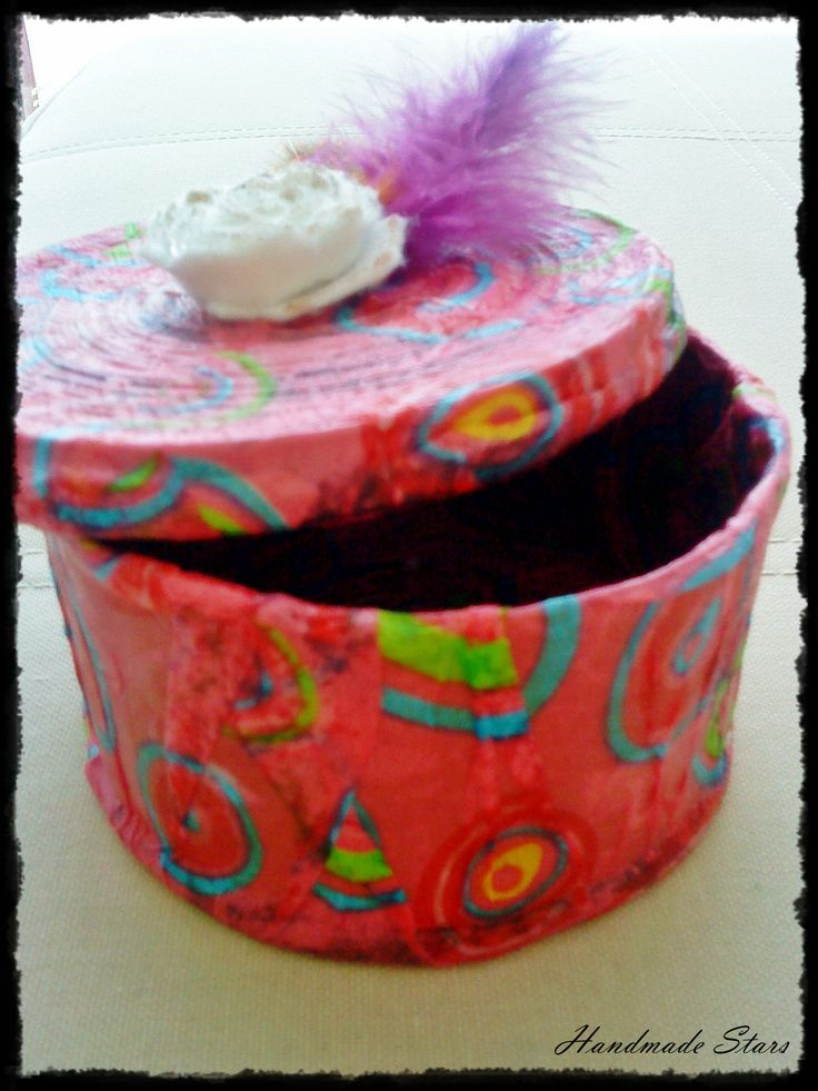 A box made by cartonboard and newspapers for the base and the box lid. It is decorated with the decoupage technic, a felt flower and colorful feathers