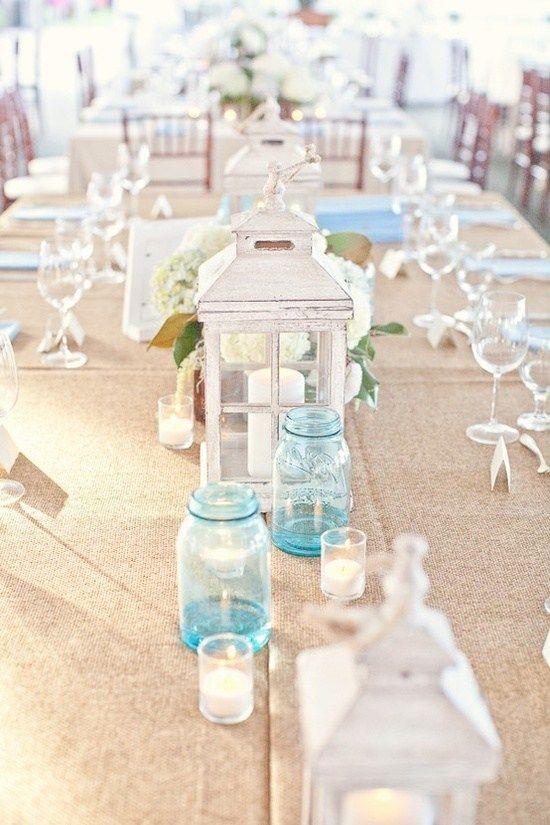 burlap blue mason jars and white lanterns via how to decorate for beach wedding via emmalinebride.com