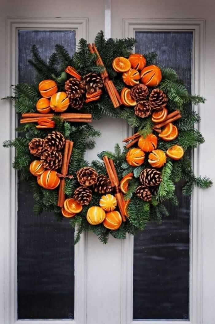 bricolage hiver de l'Avent - une grande couronne de porte en branches de conifères décorée de pommes de pin, bâtons de cannelle et oranges